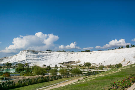 carbonates: white travertine hill Pamukkale view with blue cloudy sky and green grass and trees around