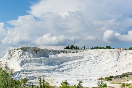 carbonates: white travertine rock view with blue cloudy sky and green grass and trees around - Pamukkale
