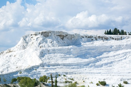 white travertine landscape view with blue cloudy sky and green grass and trees around - Pamukkale