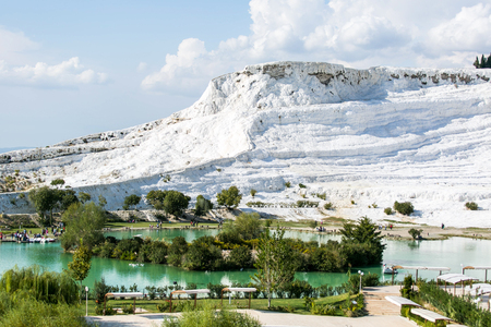 carbonates: white travertine hill and lake with blue cloudy sky and green grass and trees around - Pamukkale