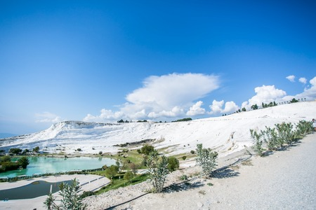 carbonates: white travertine hill and lake landcape with blue cloudy sky and green grass and trees around - Pamukkale Stock Photo
