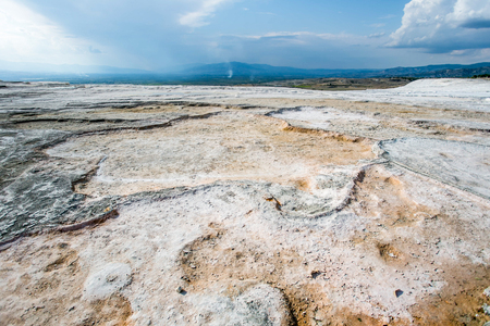 carbonates: white textured wall on the travertine hill with blue cloudy sky - Pamukkale Stock Photo