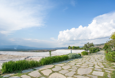 travertine: Stone and green grass alley before travertine hills at sunny day with cloudy white-blue sky - Pamukkale