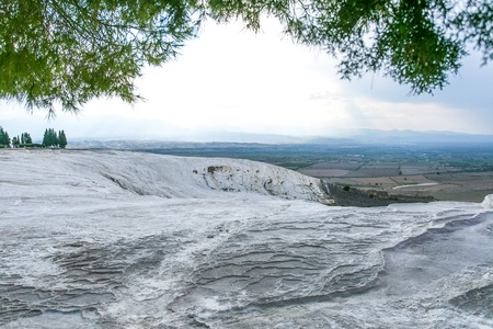 grey textured travertine hill under green trees with blue-white cloudy sky - Pamukkale