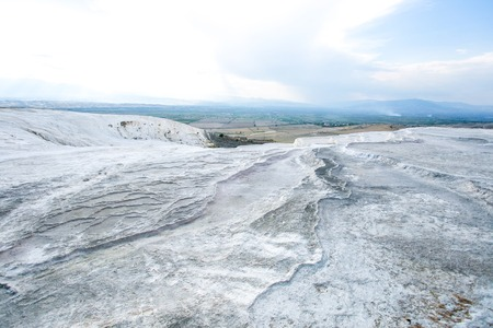 grey textured travertine hill with blue-white cloudy sky - Pamukkale