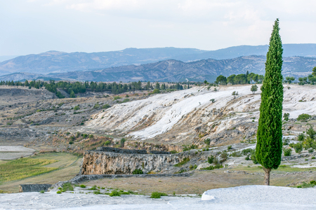 carbonates: white travertine hill view with blue cloudy sky and fir trees