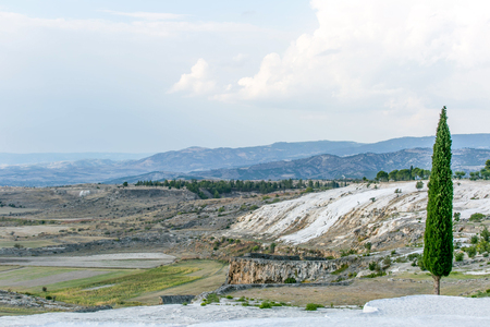 carbonates: white travertine rock view and hills with blue cloudy sky and fir trees