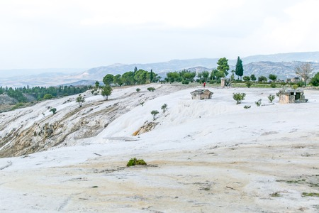 travertine: White travertine hills with green trees with blue cloudy sky - Pamukkale Stock Photo