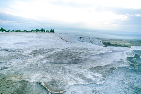 carbonates: Peak of the travertine grey color hill  with blue-white cloudy sky - Pamukkale, Turkey