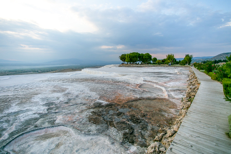 grey textured travertine hill landscape with green trees and bushes and blue-white cloudy sky - Pamukkale, Turkey
