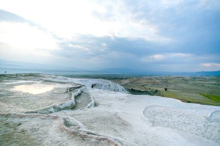 grey textured travertine dry out pools on top of the hill with blue-white cloudy sky - Pamukkale, Turkey Stock Photo