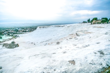 carbonate: Panoramic view of  white travertine pools and terraces with lake below and town around - Pamukkale, Turkey