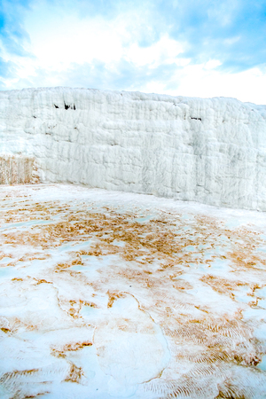 white textured wall on the travertine hill with blue cloudy sky - Pamukkale, Turkey