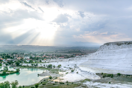 carbonate: small town around turquois lake and white travertine hills and sun peek from the clouds background - Pamukkale, Turkey