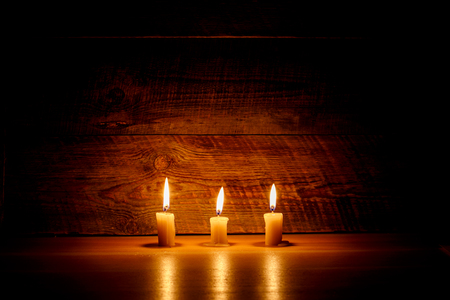 flame background: Background with candles light on wood in dark Stock Photo