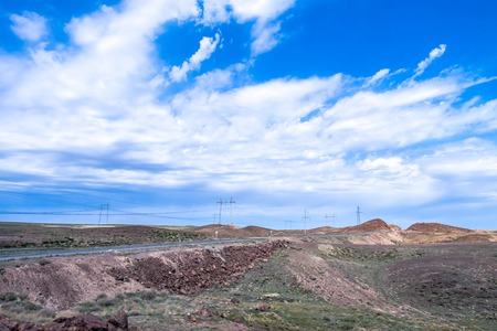 desolate: Highway through a desolate landscape with beautiful clouds and blue sky