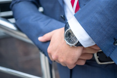 stylish men: Close up shot of businessman hands, Man in suite, watches. Waiting for somebody