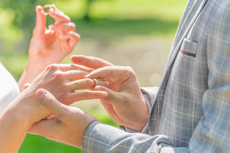 fingers put together: grooms hand putting a wedding ring on the brides finger