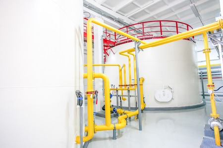 Modern factory cistern for liquid. White, yellow and red colors