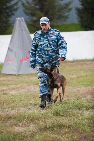 canine: Omsk, Russia - August 22, 2014: Canine Center.  German shepherd train with policeman Editorial