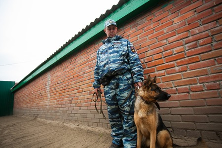 canine: Omsk, Russia - August 22, 2014: Canine Center. German shepherd and policeman at the yard