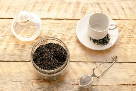 preperation: Tea set on the wooden table with cup and percolator at sunny morning at home
