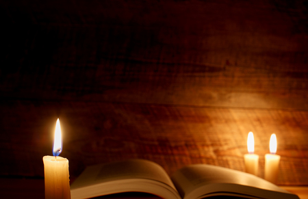 Open book with candlelight in front of wooden wall