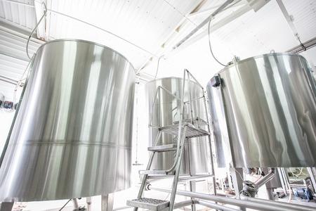 晴れた日で生乳の近代的な工場で鋼の新しい大きいタンク