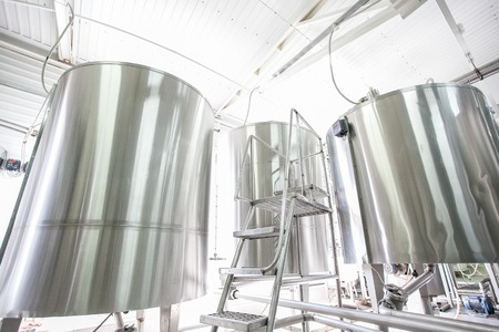 Steel nieuwe grote vaten op rauwe melk moderne fabriek op zonnige dag Stockfoto