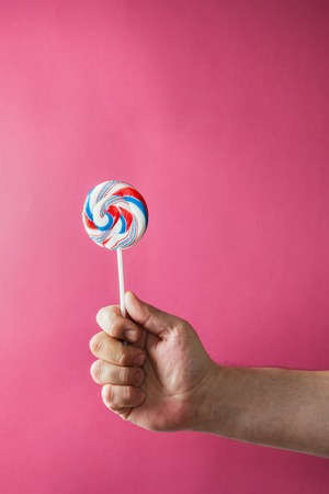 lolli: sweet round tricolor swirl candy in mans hand on the pink background