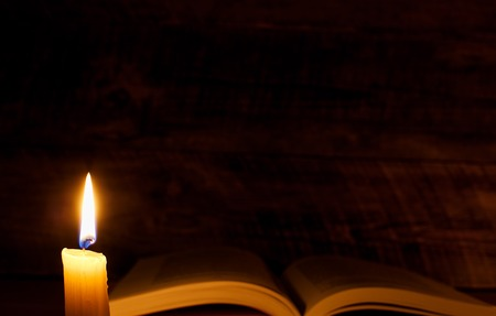 big bible: book on a wooden table by candlelight at night Stock Photo