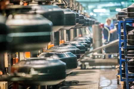 automobile industry: workpiece of car tires on the line at factory work in progress Stock Photo