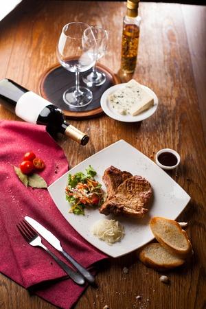 carne asada: cena gourmet de filete de ternera a la plancha con verduras y el vino en la mesa de madera de cerca