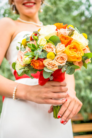 bouqet: Smiling bride with wedding bouqet with white, beige, orange and pink roses close up Stock Photo
