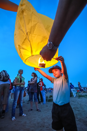 afloat: Omsk, Russia - June 16, 2012: festival of Chinese paper lantern, boy starts the lantern in the sky