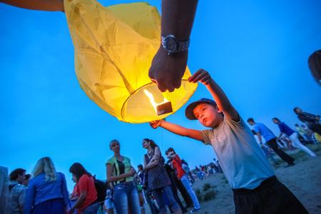 paper lantern: Omsk, Russia - June 16, 2012: festival of Chinese paper lantern, boy starts the lantern in the sky