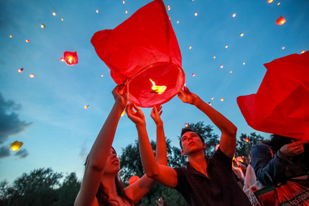 paper lantern: Omsk, Russia - June 16, 2012: festival of Chinese paper lantern, the man starts lantern in the sky at night