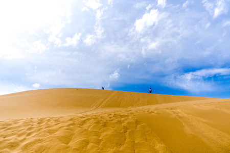 horizontally: two people walking along the top of dune under cloudy sky horizontally