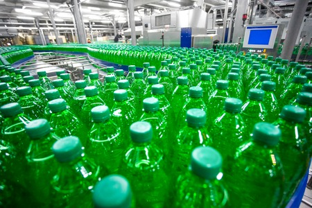 bright new factory line with plenty plastic green bottles with soda