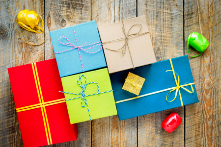 preperation: Colored gift boxes on wooden background with ribbon and straw - preperation.