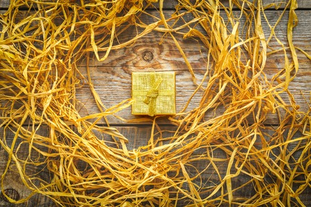 raffia: Golden gift box on wooden table with natural raffia or twine.