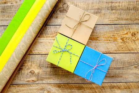 preperation: Colored craft gift boxes on wooden background with ribbon and straw - preperation. Stock Photo