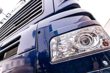 Front light of a modern truck - xenon light bulbs, steps and front bumper close up