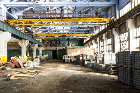 urban decline: Old abandoned industrial interior of factory warehouse with forgotten stuff at sunny day