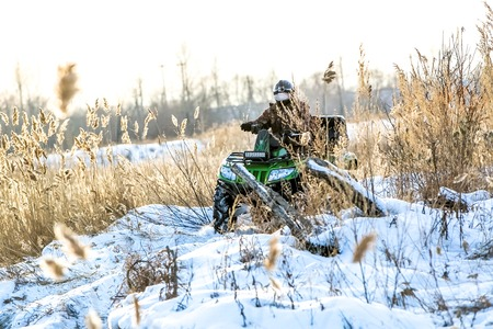 flashy: green flashy quad bike on a winter in field