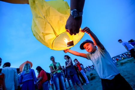 flying float: Omsk, Russia - June 16, 2012: festival of Chinese paper lantern, boy starts the lantern in the sky