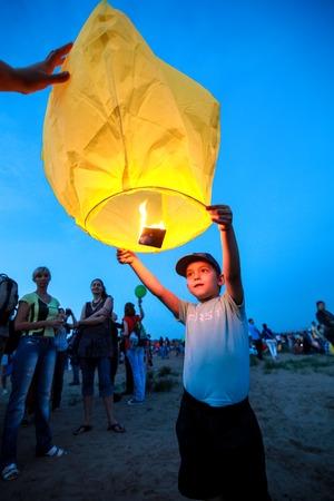 paper lantern: Omsk, Russia - June 16, 2012: festival of Chinese paper lantern, boy starts the lantern in the sky upright Editorial