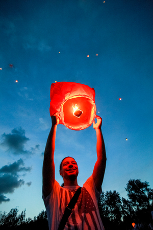 afloat: Omsk, Russia - June 16, 2012: festival of Chinese paper lantern, the man starts lantern in the sky at night