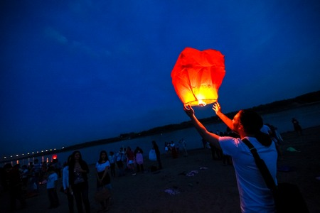 festival moments: Omsk, Russia - June 16, 2012: festival of Chinese paper lantern, the man starts lantern in the sky at night