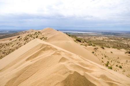 solitariness: sand dune with bushes on a background of mountains under cloudy sky close up Stock Photo